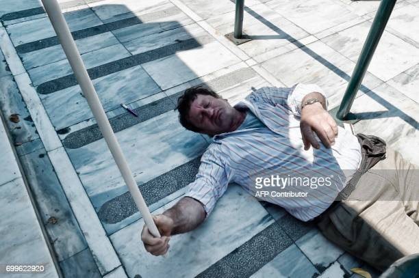 TOPSHOT A contract municipal worker lays on the ground after inhaling tear gas at the entrance to the Greek parliament in Athens during a protest on...