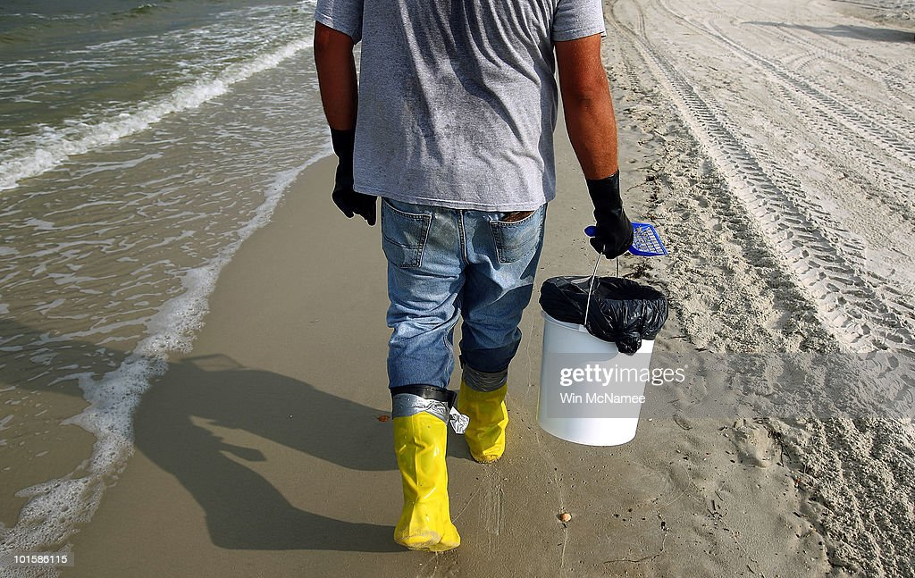 A contract worker hired by BP patrols the shore for oil to collect June 3, 2010 in Dauphin Island, Alabama. Oil related to the Deepwater Horizon accident began to appear two days ago on the shores of Alabama and recent projections indicate the Florida panhandle could be next.