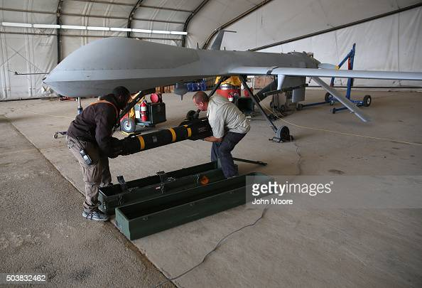 Contract workers load a Hellfire missile onto a US Air Force MQ1B Predator unmanned aerial vehicle at a secret air base in the Persian Gulf region on...