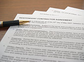 Independent Contractor Agreement Document with a pen to sign