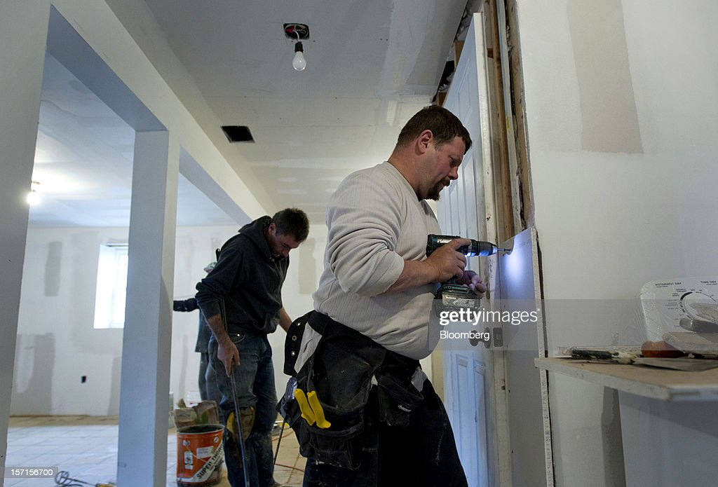 Contractor Aleksander Lewinski repairs the wall of a home in the Staten Island borough of New York, U.S., on Wednesday, Nov. 28, 2012. Superstorm Sandy is giving the U.S. Northeast, and the rest of the country, an economic boost that may eventually surpass the loss of business it caused. Photographer: Jin Lee/Bloomberg via Getty Images