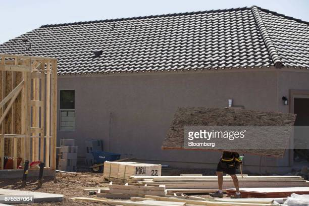 A contractor carries plywood while working on a home under construction at the DR Horton Express Homes Magma Ranch housing development in Florence...