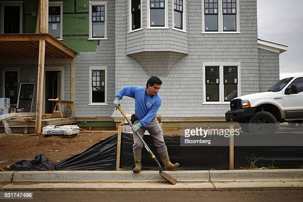 A contractor cleans mud from the gutter next to a house under construction in the Norton Commons subdivision of Louisville Kentucky US on Thursday...