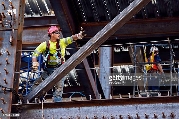 A contractor guides a steel beam into place while working on the Korean Air Lines Co Wilshire Grand hotel and office building in downtown Los Angeles...