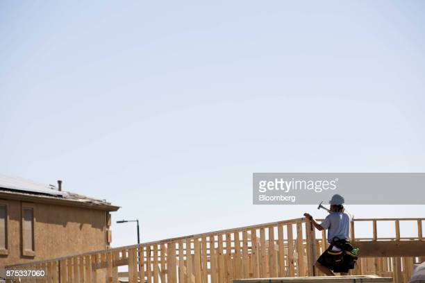A contractor hammers the frame of a home under construction at the DR Horton Express Homes Magma Ranch housing development in Florence Arizona US on...