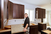 Contractor installing a new laminate kitchen counter top Kitchen more functional with a sink, cooktop,