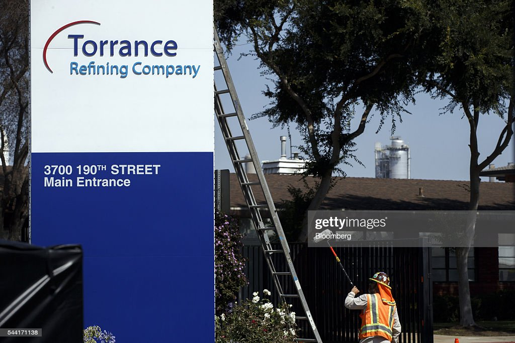 A contractor installs a new Torrance Refining Co. sign outside of the oil refinery in Torrance, California, U.S., on Thursday, June 30, 2016. Exxon Mobil Corp. completed the sale of the Torrance refinery to PBF Energy on July 1. Photographer: Patrick T. Fallon/Bloomberg via Getty Images