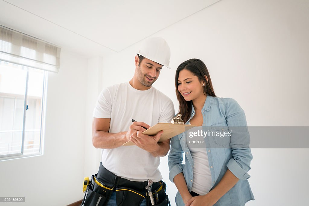 Contractor talking to a woman at home : Stock Photo