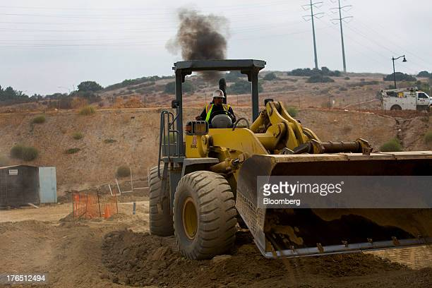 A contractor uses a bulldozer to move dirt while working on construction of the Shea Homes Frame Focus development in San Diego California US on...