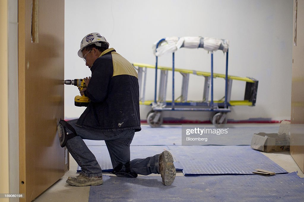 A contractor uses a drill to secure a door at Skanska USA Building Inc.'s Inova Health System construction site in Lorton, Virginia, U.S., on Thursday, Jan. 3, 2013.Construction spending dipped 0.3 percent in November as gains in housing were not enough to offset declines in nonresidential and public construction, according to Census Bureau data released Jan. 2. Photographer: Andrew Harrer/Bloomberg via Getty Images