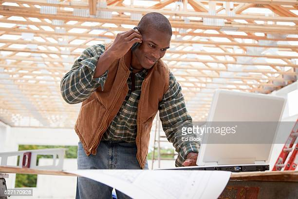 Contractor using cell phone and laptop at build site