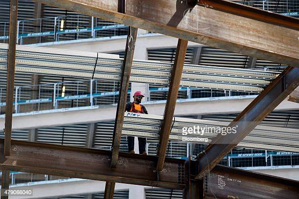 A contractor walks on a steel beam while working on the Korean Air Lines Co Wilshire Grand hotel and office building in downtown Los Angeles...