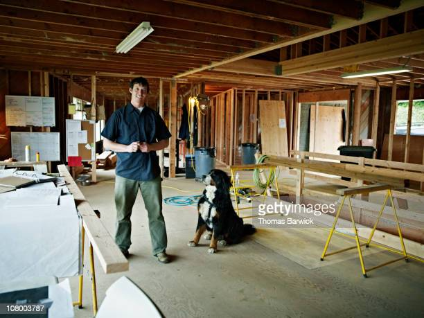 Contractor with dog in home under construction