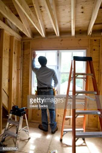 Contractor working on window in new home : Stock Photo