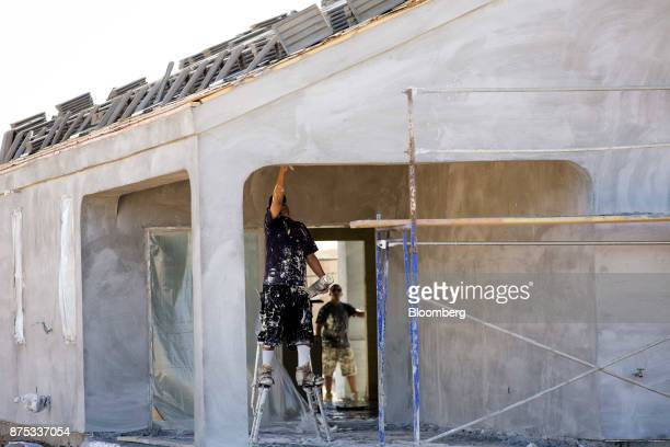 A contractor works on a home under construction at the DR Horton Express Homes Magma Ranch housing development in Florence Arizona US on Thursday Nov...