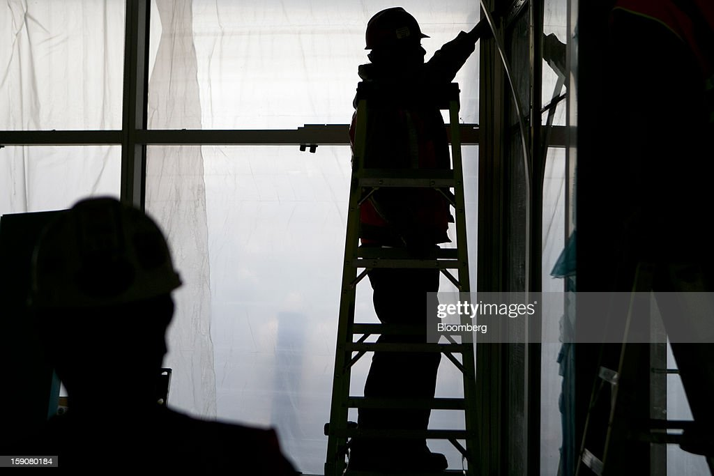 Contractors are silhouetted while working at Skanska USA Building Inc.'s Inova Health System construction site in Lorton, Virginia, U.S., on Thursday, Jan. 3, 2013. Construction spending dipped 0.3 percent in November as gains in housing were not enough to offset declines in nonresidential and public construction, according to Census Bureau data released Jan. 2. Photographer: Andrew Harrer/Bloomberg via Getty Images