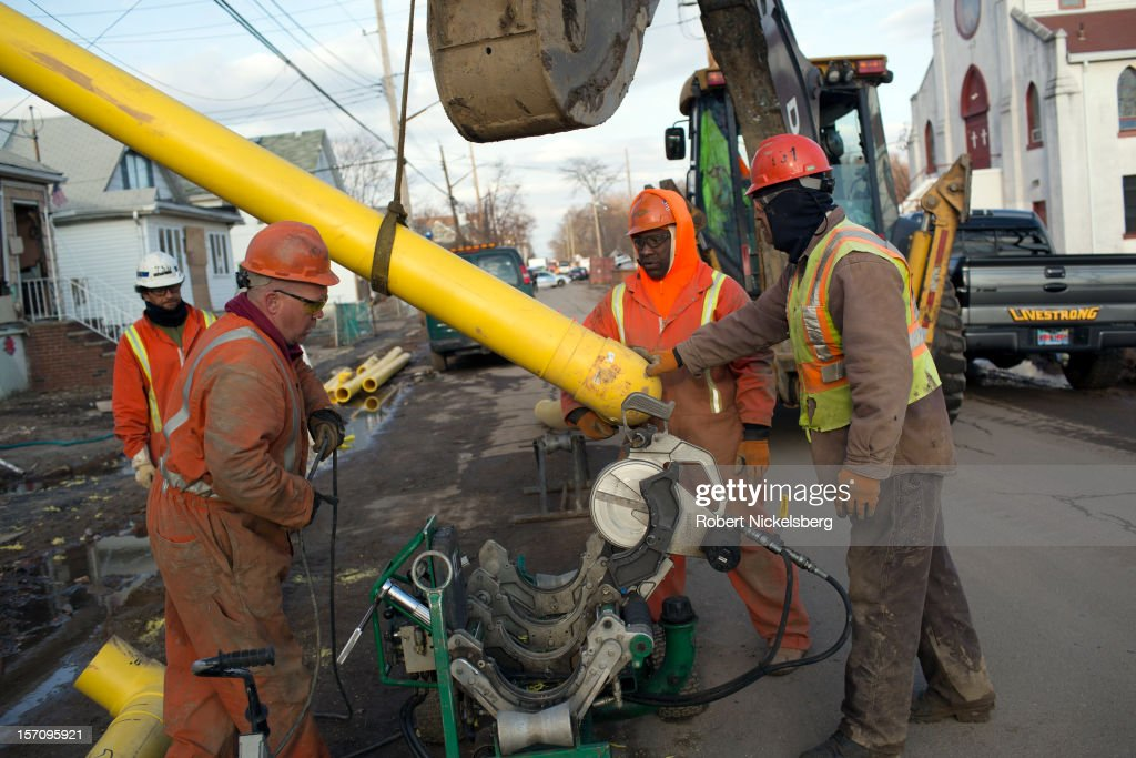 Contractors cut new natural gas pipes November 28, 2012 in a residential area of New Dorp Beach in the Staten Island borough of New York City. Parts of the New Dorp Beach neighborhood were submerged under 10 feet of water during the height of Superstorm Sandy one month ago.