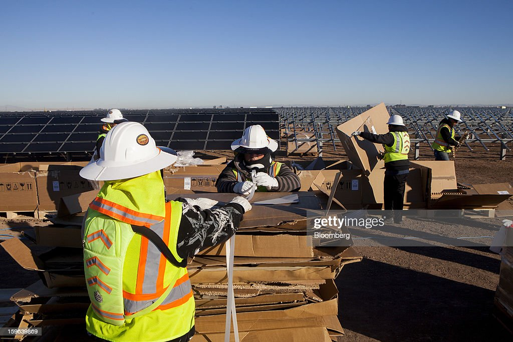 Contractors for First Solar Inc. unload materials from boxes during construction of the Tenaska Imperial Solar Energy Center South project in Imperial County, California, U.S., on Thursday, Jan. 17, 2013. The Tenaska Imperial Solar Energy Center South, when completed, will be a ground-mounted photovoltaic solar power generating system producing enough energy to meet the needs of at least 44,000 California homes, according to the Tenaska web site. Photographer: Sam Hodgson/Bloomberg via Getty Images