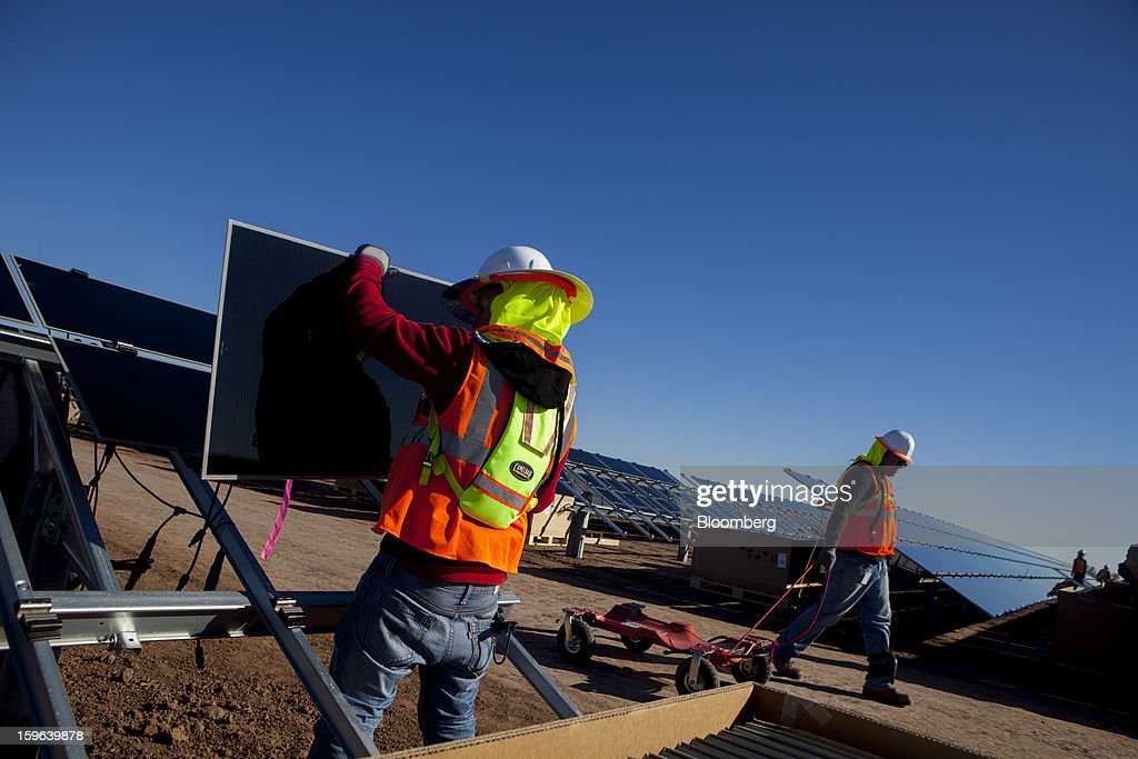 Contractors for First Solar Inc. work on construction of the Tenaska Imperial Solar Energy Center South project in Imperial County, California, U.S., on Thursday, Jan. 17, 2013. The Tenaska Imperial Solar Energy Center South, when completed, will be a ground-mounted photovoltaic solar power generating system producing enough energy to meet the needs of at least 44,000 California homes, according to the Tenaska web site. Photographer: Sam Hodgson/Bloomberg via Getty Images