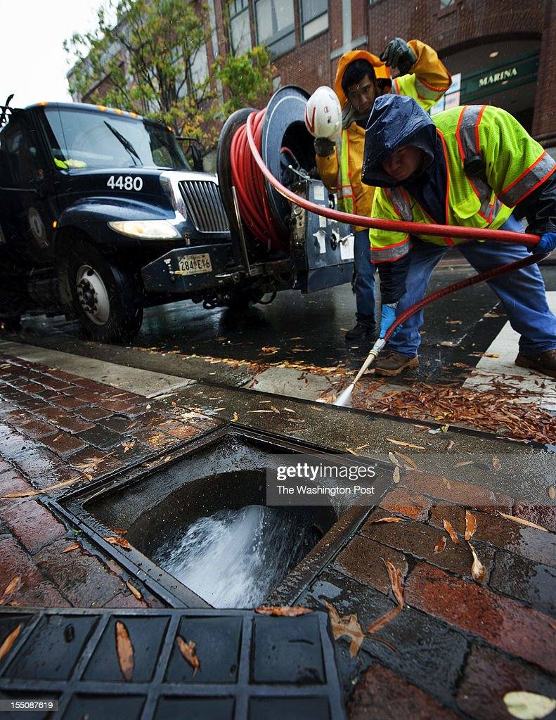 Contractors for the City Of Alexandria scrape and flush a sewer at the corner of King and Union Streets in Old Town Alexandria on Monday, October 29th, 2012. The city is trying to stay ahead of the heavy rains and flooding that is expected to take place at this intersection later tonight.