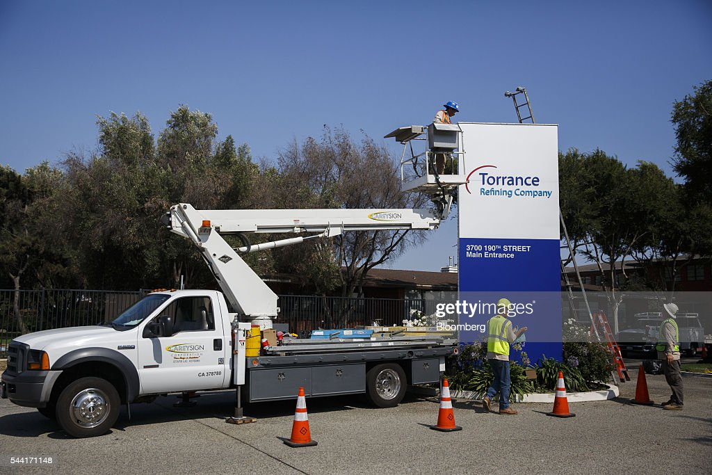 Contractors install a new Torrance Refining Co. sign outside of the oil refinery in Torrance, California, U.S., on Thursday, June 30, 2016. Exxon Mobil Corp. completed the sale of the Torrance refinery to PBF Energy on July 1. Photographer: Patrick T. Fallon/Bloomberg via Getty Images