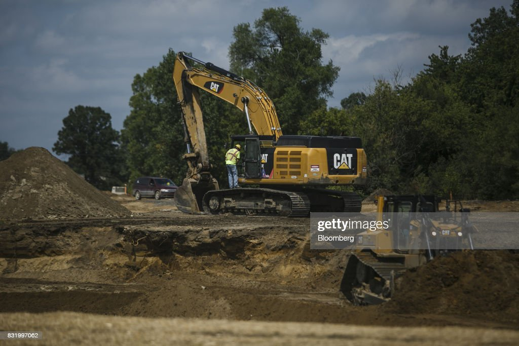 Contractors operate Caterpillar Inc. excavator and compact terrain loader on the construction site of the American Mobility Center (ACM) in Ypsilanti, Michigan, U.S., on Tuesday, Aug. 15, 2017. Representative Debbie Dingel, a Democrat from Michigan, and Representative Bob Latta, a Republican from Ohio, visited the ACM to meet with experts in the autonomous vehicles industry as the two work together to advance bipartisan self-driving vehicle legislation through the House floor. Photographer: Sean Proctor/Bloomberg via Getty Images