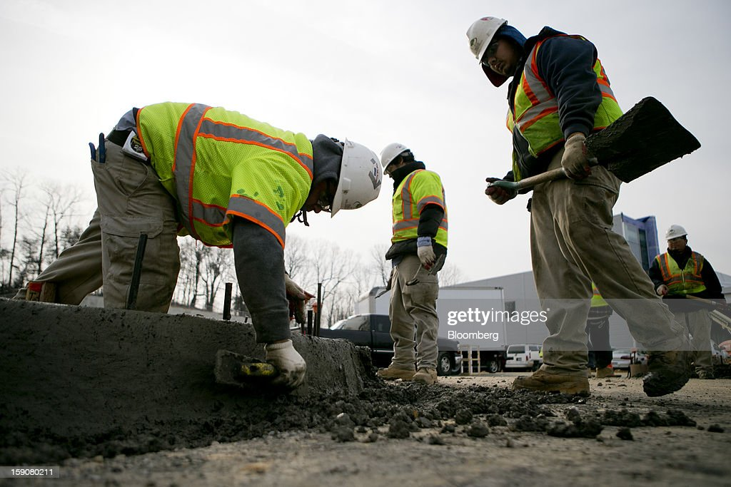 Contractors smooth the concrete on a curb at Skanska USA Building Inc.'s's Inova Health System construction site in Lorton, Virginia, U.S., on Thursday, Jan. 3, 2013. Construction spending dipped 0.3 percent in November as gains in housing were not enough to offset declines in nonresidential and public construction, according to Census Bureau data released Jan. 2. Photographer: Andrew Harrer/Bloomberg via Getty Images