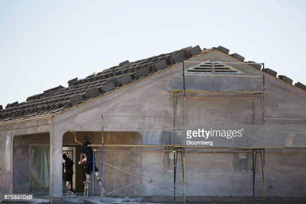 Contractors work on a home under construction at the DR Horton Express Homes Magma Ranch housing development in Florence Arizona US on Thursday Nov...