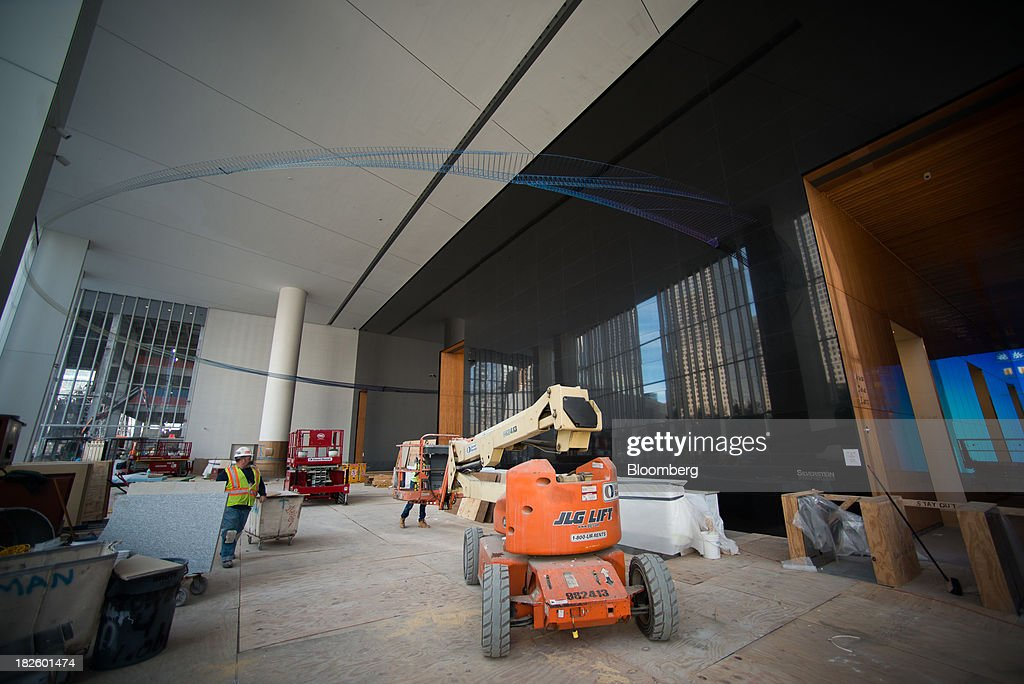 Contractors work on finishing construction on the 4 World Trade Center building, managed by Silverstein Properties Inc., in New York, U.S., on Wednesday, Sept. 25, 2013. Real estate developer Larry Silverstein cant recoup any of the $1.2 billion recovered by World Trade Center insurers in settlements with airlines and airport security companies over the Sept. 11, 2001, terrorist attack that destroyed the office complex, a judge ruled. Photographer: Craig Warga/Bloomberg via Getty Images