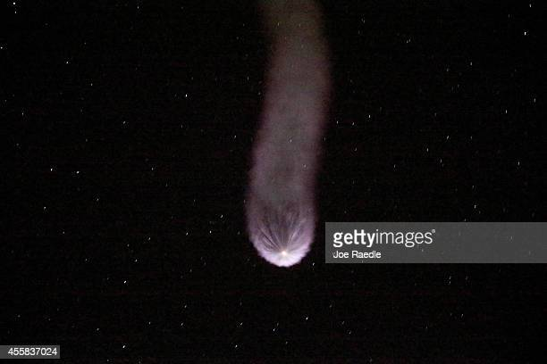 A contrail is seen behind the SpaceX Falcon 9 rocket carrying a Dragon supply ship as it flies into space after lifting off from the launch pad on a...