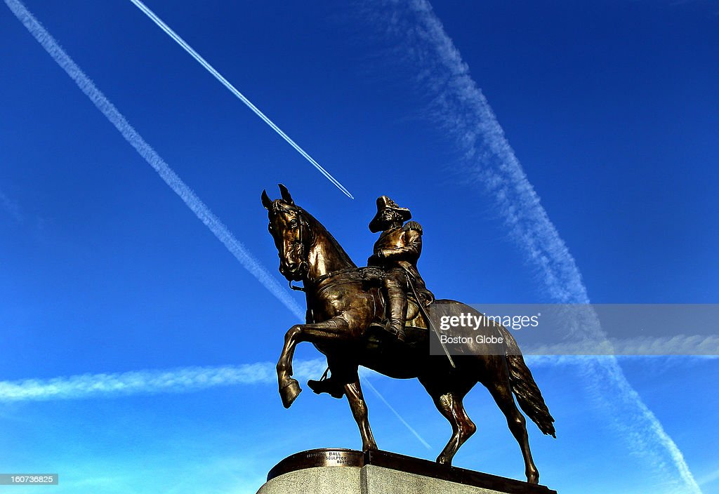 Contrails from jets form lines in the sky as seen above the statue of George Washington on his horse on the Boston Public Garden.
