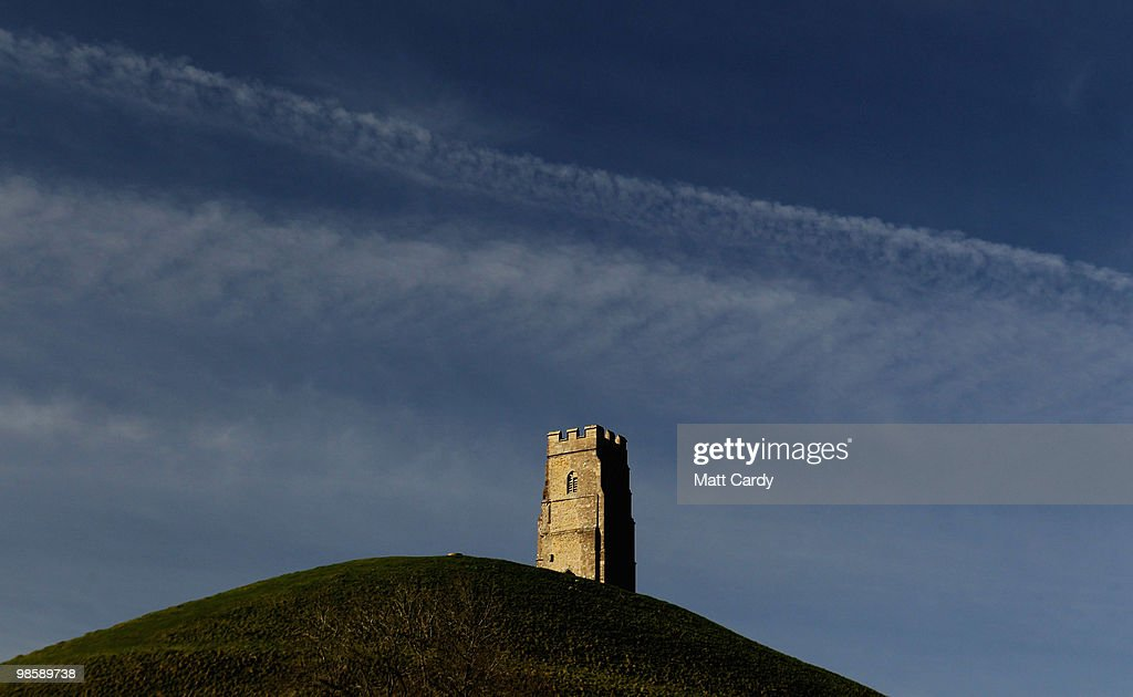 Contrails left by jet aircraft cross the sky above the distinctive landmark of Glastonbury Tor on April 21, 2010 near Glastonbury, England. Airlines are beginning to resume a normal service following six days of airport closures due to volcanic ash from Iceland covering British airspace.