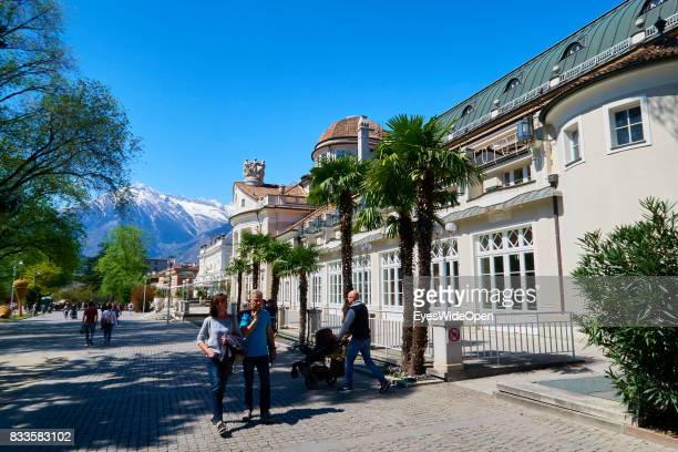 Contrast of snow and palm trees with tourists are walking next to the Kurhaus a famous Art Nouveau Building in the green city centre of Meran in...