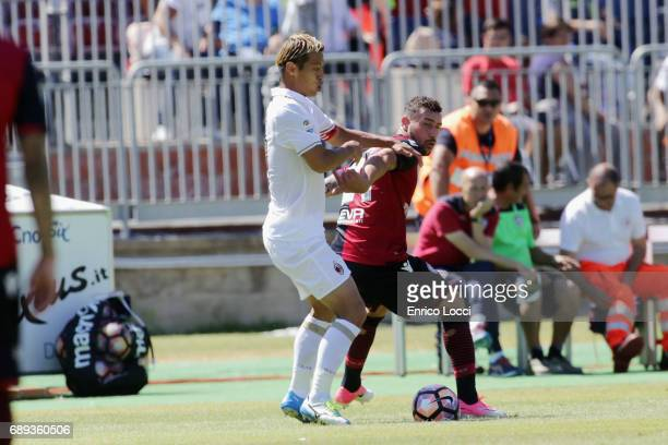Contrast with Artur Ionita of Cagliari and Keisuke Honda of Milan during the Serie A match between Cagliari Calcio and AC Milan at Stadio Sant'Elia...