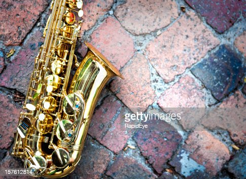 Contrasting textures: gleaming golden sax on rough raw bricks