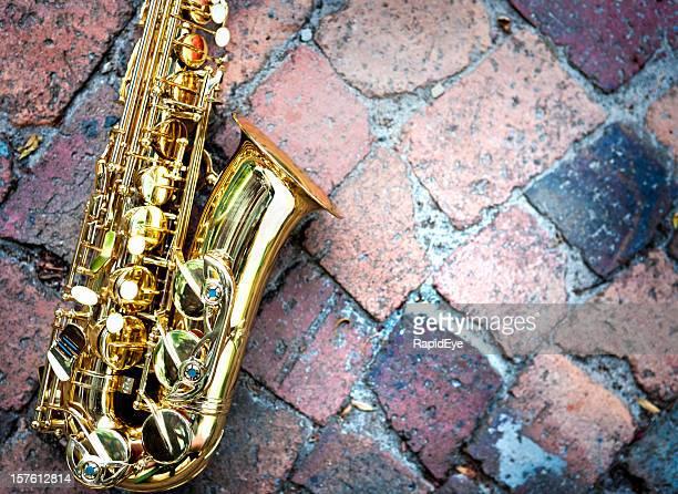 Kontrastierende Strukturen: Glänzend goldenen sax auf unebenem raw-Bausteinen spielen