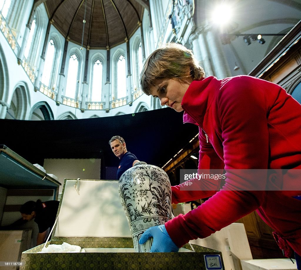 A contributor checks the art pieces from China that arrived in the New Church in Amsterdam on Septembe r19, 2013. The pieces are transported from the Nanjing Museum for a big exhibition named Ming, Emperors, Artists and Merchants in the old China. AFP PHOTO/ANP ROBIN VAN LONKHUIJSEN netherlands out