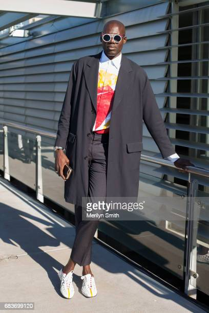 Contributor to L'Officiel Ukraine and New York Style Guide Badara Ndiaye wearing a Sandro coat Prada shoes Hugo Boss trousers and Peter and May...