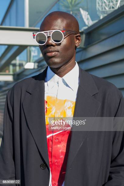 Contributor to L'Officiel Ukraine and New York Style Guide Badara Ndiaye wearing his own printed shirt Sandro coat and Peter and May sunglasses...
