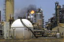 A controlled flame burns behind a storage tank in the oil refinery complex of AmuayCardon April 4 2003 in Paraguana located about 350 miles West of...