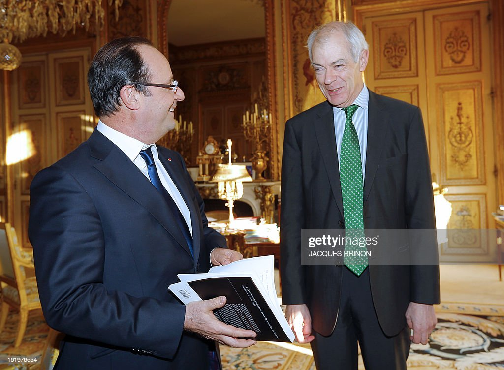 Controller general of Places of Deprivation of Liberty (CGPL) Jean-Marie Delarue (R) speaks with French president Francois Hollande after handing him over his 2012 activities report on February 18, 2013 at the Elysee Presidential palace in Paris.