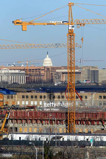 Contruction cranes stand at the damaged side of the Pentagon where rebuilding efforts continue February 11 2002 in Washington DC On September 11 a...