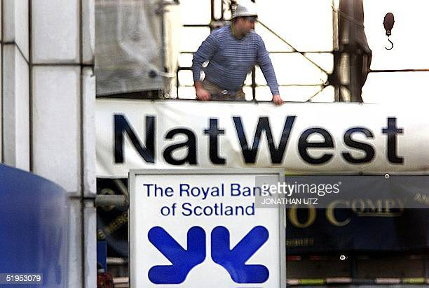 A contruction worker moves about on a scaffold surrounding a branch of NatWest Bank beside an office of the Royal Bank of Scotland in central London...