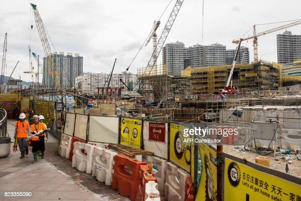 Contruction workers walk near the construction site for the West Kowloon terminus of the highspeed rail link connecting Hong Kong to the southern...