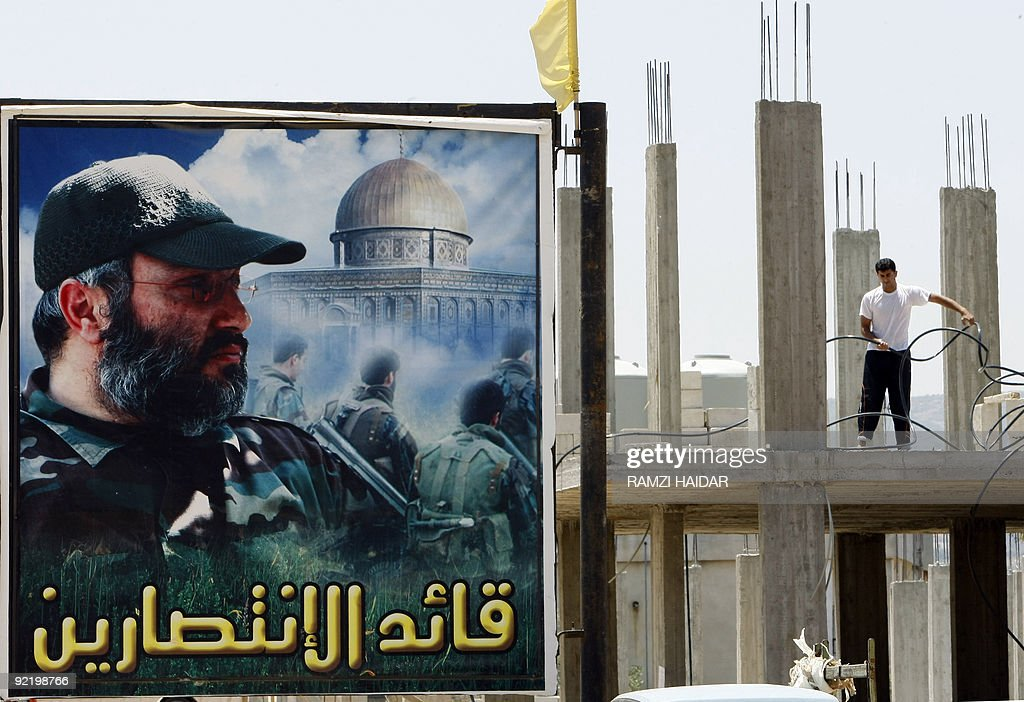 A contsruction labourer works next to a billboard bearing a portrait of slain Hezbollah commander Imad Mughnieh in the southern Lebanese village of...