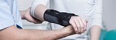 Woman with dislocated wrist in stabilizer is consulting doctor