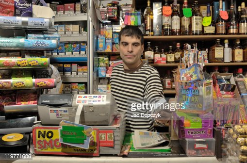 Convenience store owner handing over cigarettes. : Stock Photo