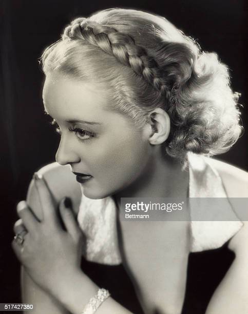 Convenient and unusual is this new hairstyle introduced by Bette Davis in the Warner Brothers film Fog Over Frisco Her medium length bob is dressed...