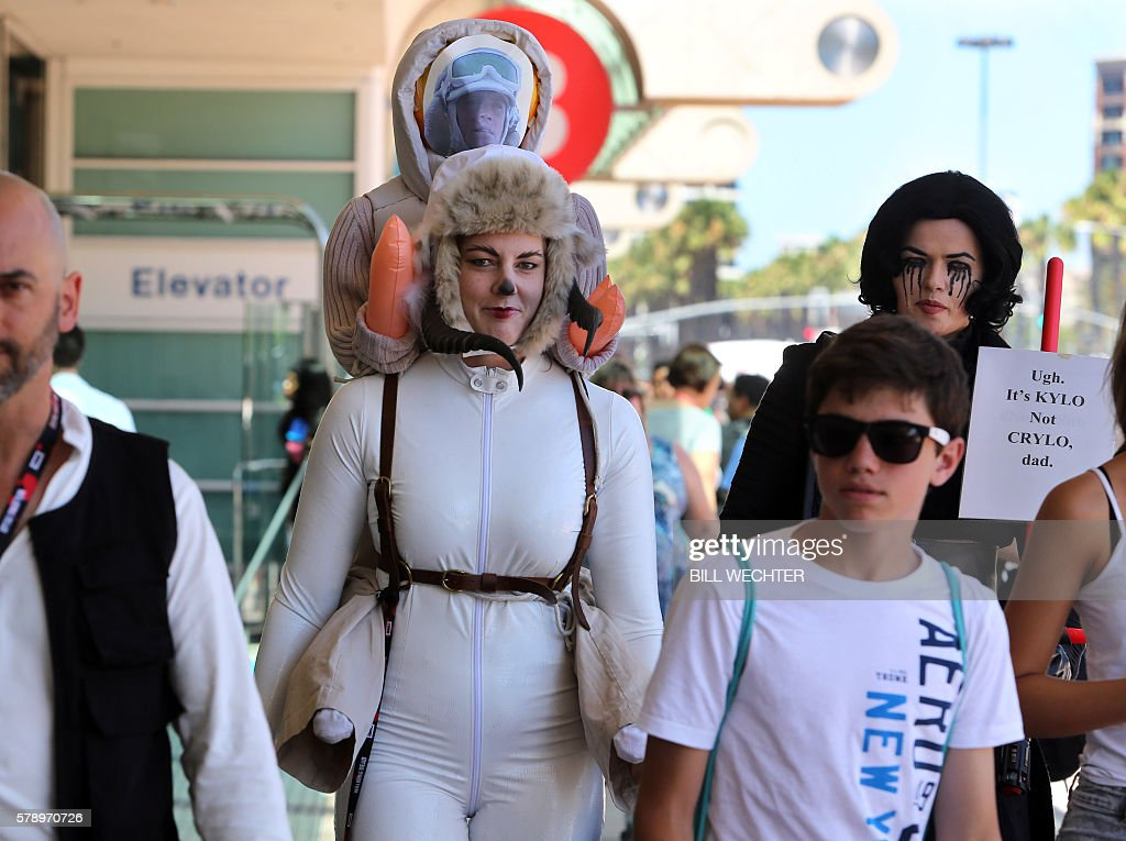 A convention attendee from San Francisco is dressed as fantasy creature from Star Wars called a tauntaun center and carries a rendition of Luke...
