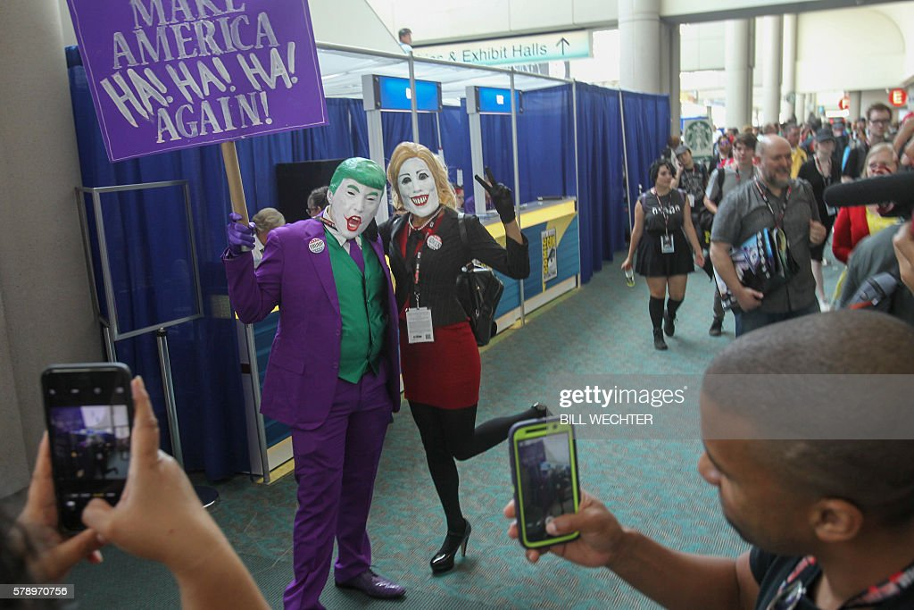Convention attendees take photos of Nick Mollberg, playing Donald Trump, and Auburn Rutledge, playing Hillary Clinton, they are both from Austin, Texas, during Comic-Con International 2016 in San Diego, California, July 22, 2016. / AFP / Bill Wechter